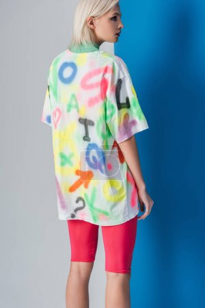 Photo for Back view of stylish girl posing in neon pink bike shorts and colorful t-shirt on grey and blue - Royalty Free Image