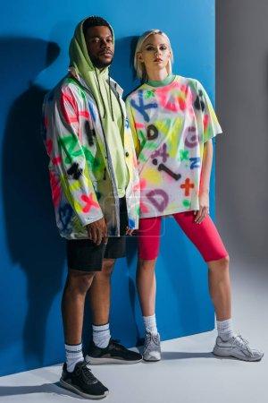 Foto de Hermosa pareja interracial colocada en colorido aspecto futurista en gris y azul. - Imagen libre de derechos