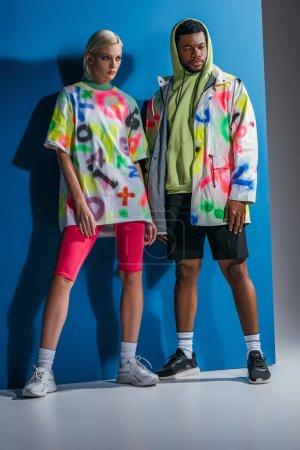 Photo pour Couple multiculturel élégant posant dans un look futuriste coloré sur gris et bleu - image libre de droit