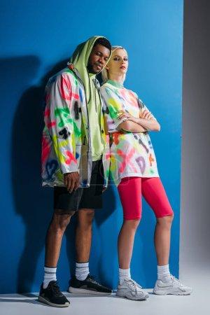 Foto de Pareja multicultural de moda que presenta un colorido aspecto futurista en gris y azul. - Imagen libre de derechos