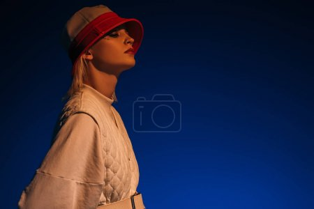 fashionable model posing in futuristic look and hat on dark blue