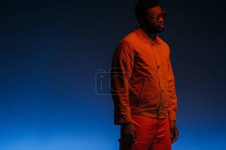 Photo pour Homme afro-américain au look futuriste et lunettes de soleil posant sur le bleu dans la lumière rouge - image libre de droit