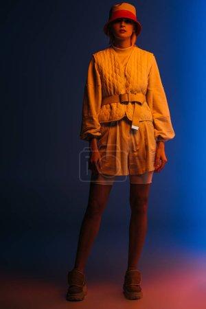 Photo pour Modèle à la mode posant dans un look futuriste et chapeau sur bleu foncé - image libre de droit