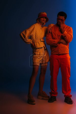 Foto de Pareja multiétnica con estilo que presenta un aspecto futurista sobre el azul bajo luz naranja. - Imagen libre de derechos
