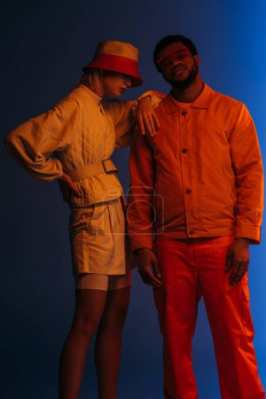 Photo for Interracial couple in futuristic clothes, sunglasses and hat posing on blue in orange light - Royalty Free Image