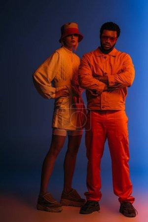 fashionable interracial couple posing in futuristic look on blue in orange light
