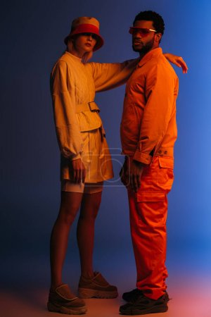 Photo pour Un couple multiculturel à la mode vêtu de vêtements futuristes, de lunettes de soleil et d'un chapeau bleu à la lumière orange - image libre de droit