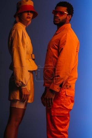 Photo pour À la mode couple multiethnique en vêtements futuristes, lunettes de soleil et chapeau posant sur bleu à la lumière orange - image libre de droit