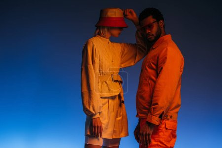 Photo for Fashionable interracial couple in futuristic clothes, sunglasses and hat posing on blue in orange light - Royalty Free Image