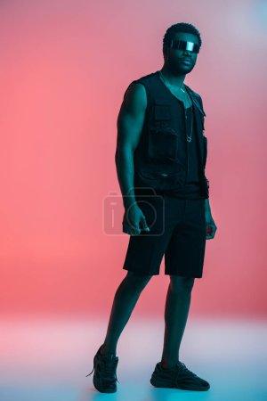 Photo pour Bel homme élégant afro-américain aux lunettes de soleil futuristes posant sur rose à la lumière bleue - image libre de droit