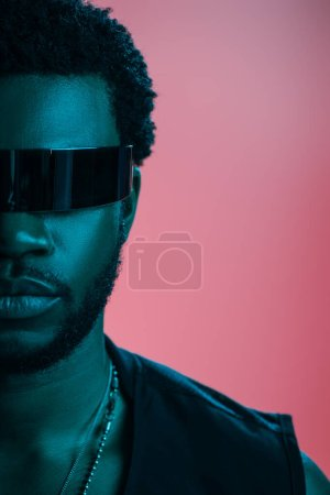 Photo for Fashionable african american man in futuristic sunglasses posing on pink in blue light - Royalty Free Image