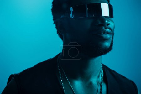 smiling african american man in futuristic sunglasses posing on blue in blue light