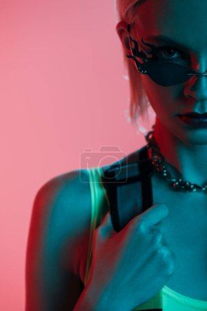 Photo for Stylish model in futuristic leotard and fire-shaped sunglasses posing isolated on pink in blue light - Royalty Free Image