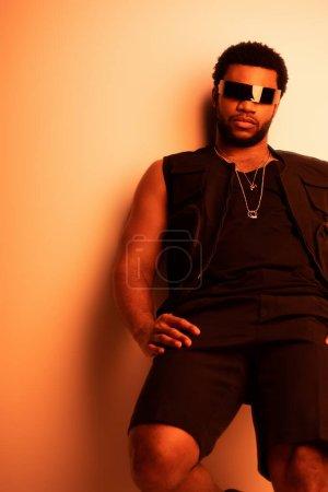 Photo pour Homme afro-américain à la mode posant dans des lunettes de soleil futuristes sur orange - image libre de droit