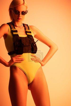 Photo pour Modèle futuriste à la mode posant dans des lunettes de soleil en forme de feu sur orange - image libre de droit