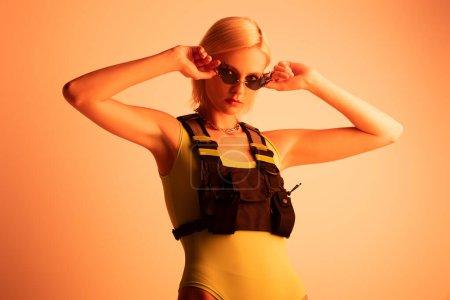 Photo pour Jeune femme futuriste à la mode posant dans des lunettes de soleil en forme de feu sur orange - image libre de droit