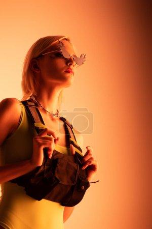 Photo pour Attrayant élégant futuriste fille posant dans des lunettes de soleil en forme de feu sur orange - image libre de droit