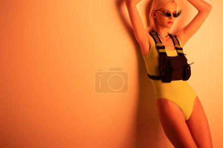 Photo for Fashionable futuristic girl posing in bodysuit and fire-shaped sunglasses on orange - Royalty Free Image