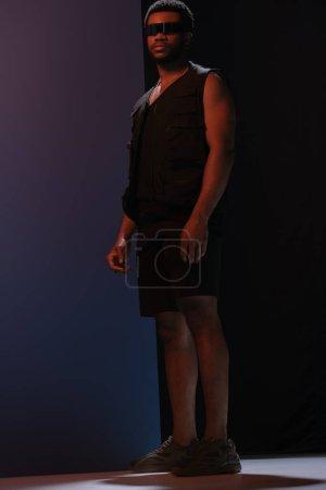 Photo pour Lunettes de soleil futuristes homme afro-américain à la mode en posant sur bleu foncé - image libre de droit