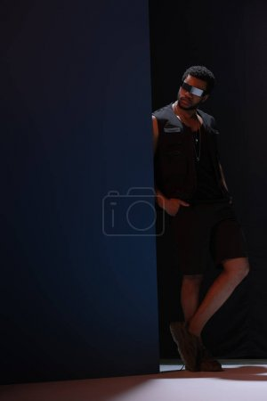 Photo pour Fashionable african american man futuristic sunglasses in posing on dark blue - image libre de droit