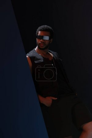 Photo pour African american male model futuristic sunglasses in posing on dark blue - image libre de droit