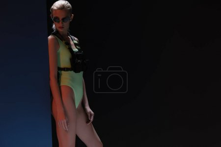 Photo for Beautiful fashionable woman in futuristic bodysuit and fire-shaped sunglasses posing on dark - Royalty Free Image