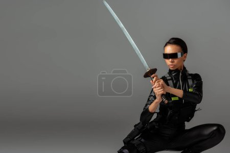Photo pour Attractive futuristic american woman in glasses sitting with sword on grey - image libre de droit