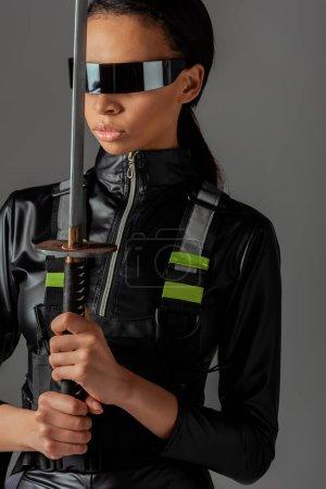 Photo pour Séduisante femme afro-américaine futuriste dans des lunettes avec épée isolée sur gris - image libre de droit