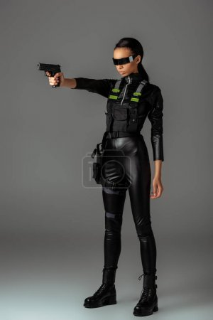 Photo for Attractive futuristic african american woman in glasses aiming gun on grey - Royalty Free Image