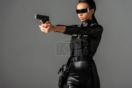 Photo for Attractive futuristic african american woman in glasses aiming gun isolated on grey - Royalty Free Image