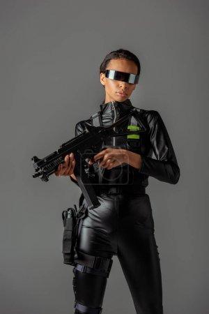 Photo pour Séduisante femme afro-américaine futuriste à lunettes avec fusil d'assaut isolé sur gris - image libre de droit
