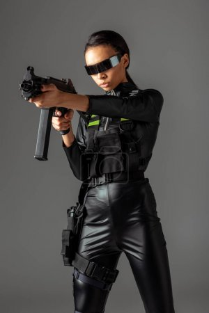 Photo for Futuristic african american woman in glasses aiming assault rifle isolated on grey - Royalty Free Image