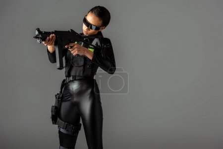 Photo for Futuristic african american woman in glasses aiming assault rifle on grey - Royalty Free Image