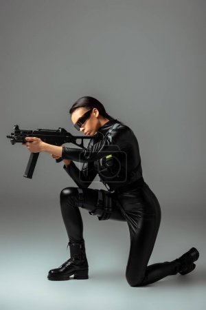 Photo for Futuristic african american woman in glasses aiming assault rifle while standing on knee on grey - Royalty Free Image