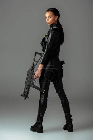 Foto de Futurista afriamericana con futurista rifle de asalto sobre gris. - Imagen libre de derechos
