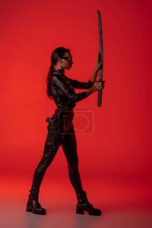 Foto de Vista lateral de la futurista africaica americana en gafas con espada sobre fondo rojo. - Imagen libre de derechos