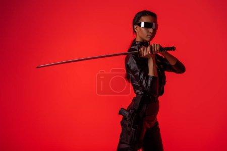 Photo pour Attrayante américaine futuriste américaine en lunettes avec épée isolée sur rouge - image libre de droit