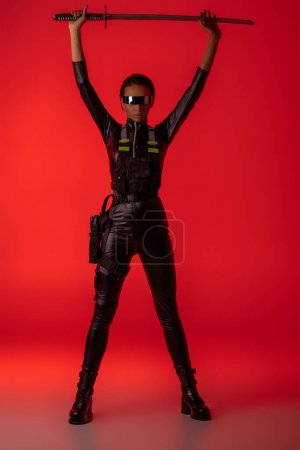 Photo pour Attractive futuristic american woman in glasses with sword above head on red background - image libre de droit