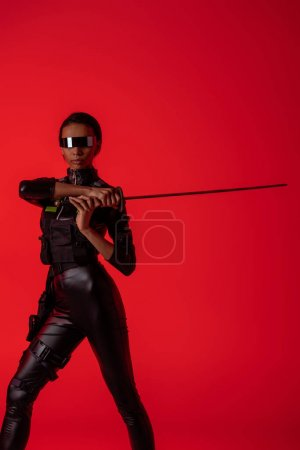Photo pour Attrayante américaine futuriste américaine en lunettes avec épée isolée sur fond rouge - image libre de droit