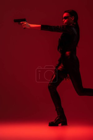 Photo for Futuristic african american woman in glasses aiming gun on red background - Royalty Free Image