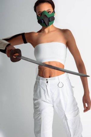 Photo pour Futuriste afro-américaine en masque de sécurité avec épée sur fond blanc - image libre de droit