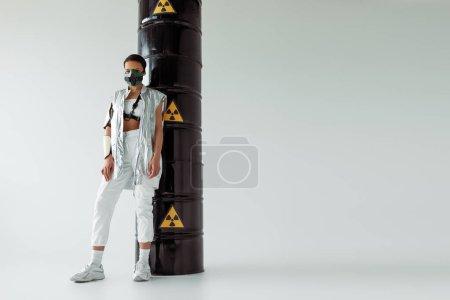 Photo pour Futuriste afro-américaine masque de sécurité près de barils de déchets radioactifs sur fond blanc - image libre de droit