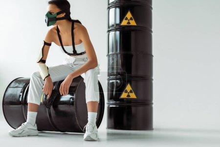 Photo pour Femme afro-américaine futuriste en masque de sécurité avec arme à feu près de barils de déchets radioactifs sur fond blanc - image libre de droit