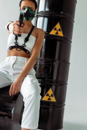 Photo pour Foyer sélectif de femme afro-américaine futuriste en masque de sécurité visant pistolet près de barils de déchets radioactifs sur fond blanc - image libre de droit