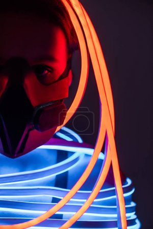Foto de Vista recortada de la mujer afroamericana futurista en respirador e iluminación de neón - Imagen libre de derechos