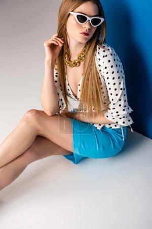 Photo pour Belle fille posant en chemisier à pois, jupe bleue et lunettes de soleil sur gris et bleu - image libre de droit