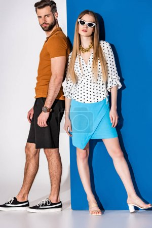 Photo for Fashionable young couple posing in summer clothes and sunglasses on grey and blue - Royalty Free Image