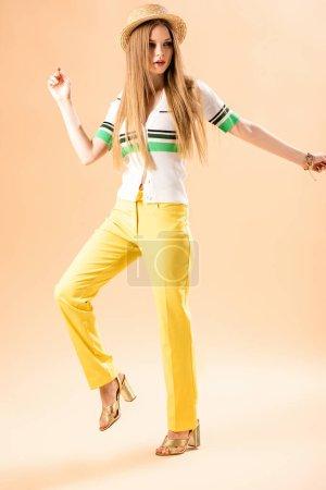 Photo pour Belle fille à la mode posant en pantalon jaune, polo et chapeau de paille sur beige - image libre de droit