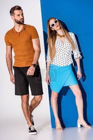 Photo pour Beau couple à la mode posant en vêtements d'été et lunettes de soleil sur gris et bleu - image libre de droit