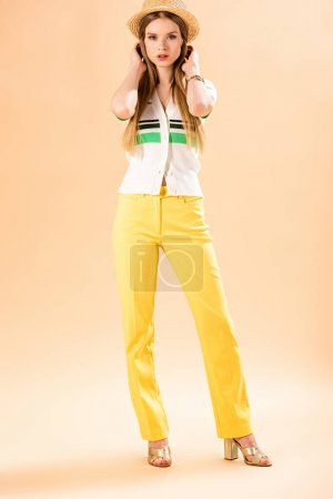 Photo for Attractive stylish woman posing in yellow trousers, polo and straw hat on beige - Royalty Free Image